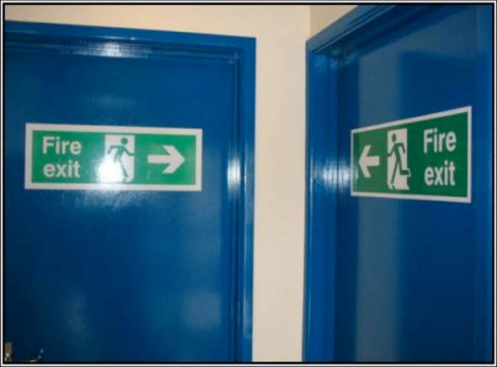Fire exit signs pointing to a corner